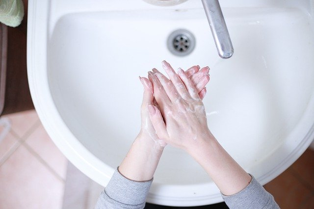 Woman washing hands to limit spread of coronavirus